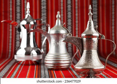 Three ornate Dallah are placed on traditional red fabric from the Middle East. Dallah is a metal pot for making tea and coffee
