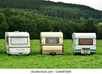 Three outdated caravans lined up at a campsite in the Belgian Ardennes.