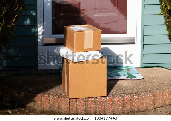 Three packages are delivered to the frint stoop of a residential house.