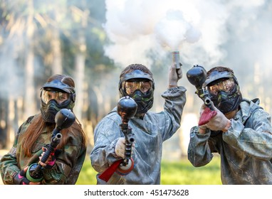 Three paintball players with guns and smoke grenade aiming in camera