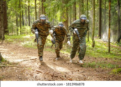 Three paintball players running with paint guns