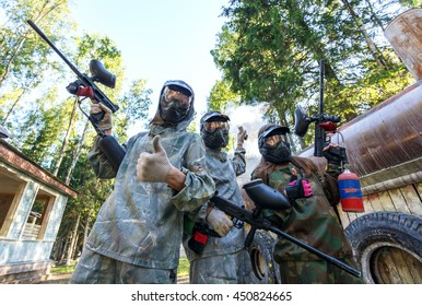 Three paintball players with smoke grenade posing in masks outdoors