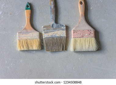 Three paintbrush on the gray concrete with copy space