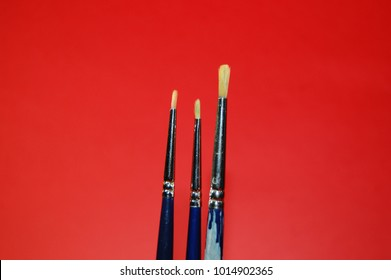 Three paintbrushes on a red background