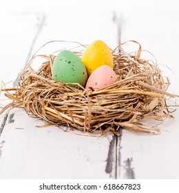 Three painted easter eggs in a birdnest