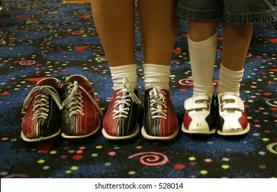 Three pair of bowling shoes. Two being worn, one empty.
