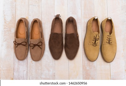 Three pair men's comfortable footwear.Brown male loafer brown suede shoes isolated over wooden background