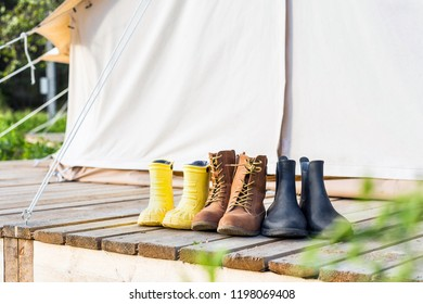 Three pair of shoes on wooden terrace near a canvas tent. Family trip concept