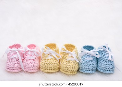 Three pairs of baby booties on a white background