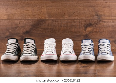 three pairs of cool youth white gym shoes with red  stripes  on brown wooden floor  standing in line with copy place