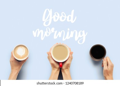 Three pairs of hands are holding cups of coffee on a blue background. Concept breakfast with friends, friendly company. Flat lay, top view