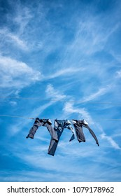 Three pairs of jeans drying on a sunny day from a clothesline