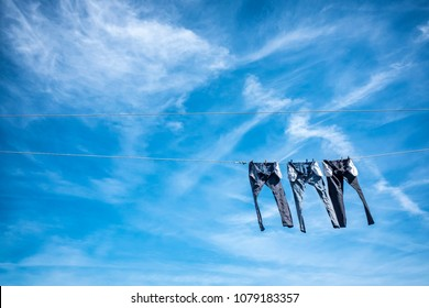 Three pairs of jeans drying on a sunny day from a clothesline, with space for copy.