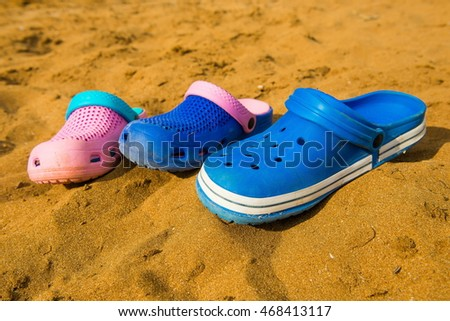 dbb4f5d99343a Three pairs of shoes on the beach sand. Family holiday. slippers