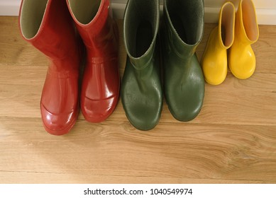 Three pairs of wellies by the wall