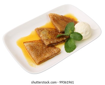 three pancakes with orange sauce, mint twig and scoop of vanilla ice cream in rectangular dish isolated on a white background