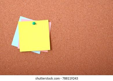 Three paper note blank card on cork board.