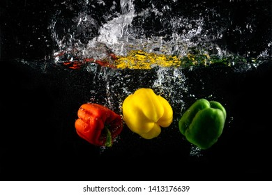 Three Paprika splash in water on black background, Capsicum annuum: bell pepper and buble.
