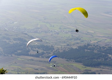 Three paraglider flies paraglider over the valley in summer sunny day