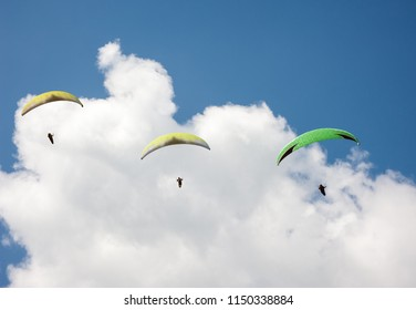 Three paragliders flying in the blue sky against the background of clouds. Paragliding in the sky on a sunny day.