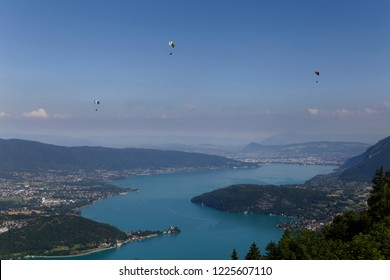 Three paragliders flying high over Lake Annecy France