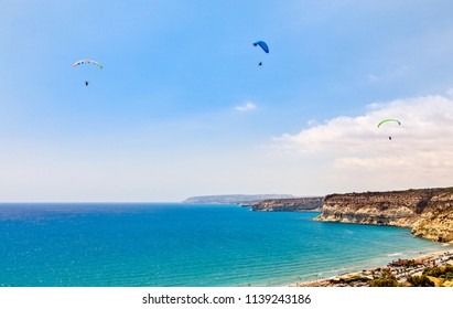 Three paragliders flying over the Kurion beach and mediterranean sea landscape, Limassol, Cyprus