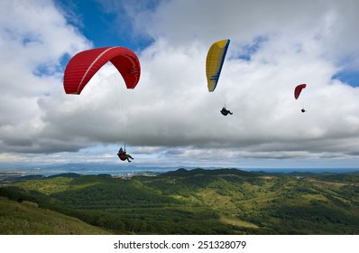 Three paragliding over the green valley.