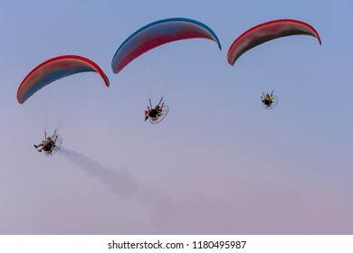 Three paramotors flying against the sky painted in the colors of a beautiful sunset