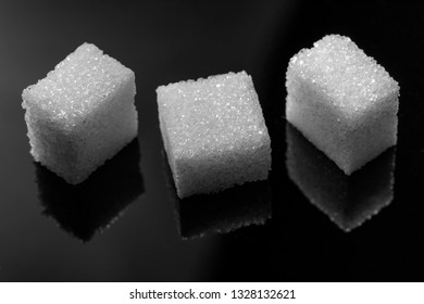 three peaces cube sugar on black background