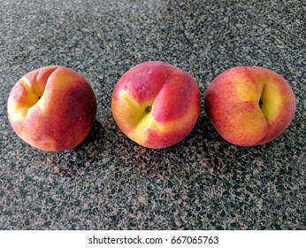 three peaches on kitchen counter