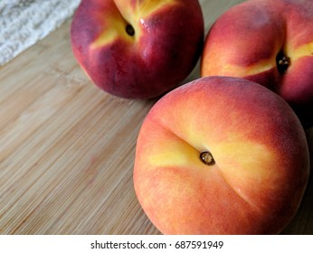 three peaches on wooden cutting board