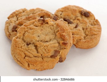 three peanut butter chocolate chunk cookies on white background