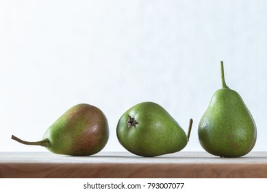 three pears against a clean background showing skin and stalk detail