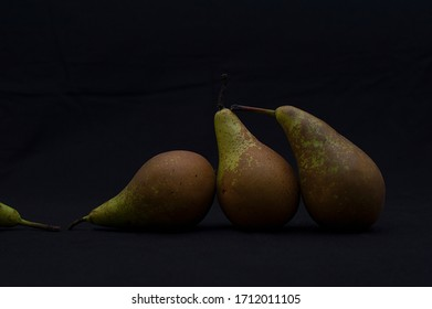 three pears together leaning towards a fallen one