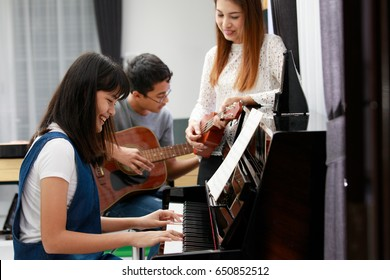 Three people Asian family, mother son and daughter playing music together. Piano, guitar and ukulele in family band at home