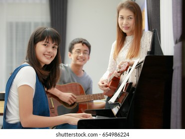 Three people Asian family, mother son and daughter playing music together. Piano, guitar and ukulele in family band at home, concept for family relationship
