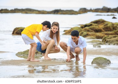 three people Asian family on vacation, mother and sons,  playing on tropical beach  with funny and happiness.
