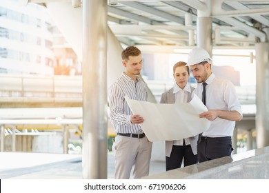 Three people are business manager and engineer meeting project at construction site. Man wearing safety helmet and holding blueprint document.