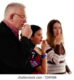 Three people of a congregation taking the bread together during communion.