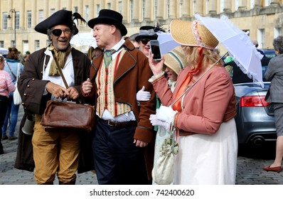 Three people dressed vintage costume at the Regency Costumed Promenade,the 200th anniversary of Jane Austen's death in Bath,Royal Crescent,England.09/09/2017