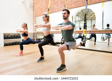 Three people exercising suspended lunge using trx at gym