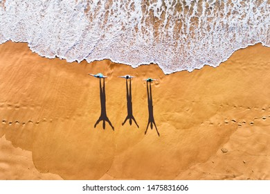 Three people facing rolling waves of Pacific ocean on a clean wide sandy beach during morning exercise in aerial top down view.