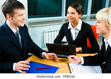 Three people gathered together around the table and discuss ideas at business meeting