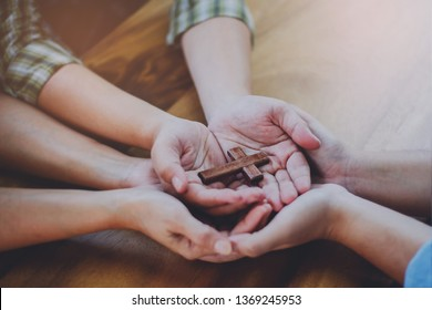 Three people hands holding small wooden cross on wood table, Christian concept Jesus is the center of life or ministry , copy space.