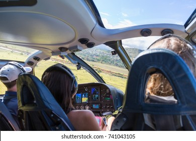 Three people in a helicopter cabin in mid flight over Kauai, Hawaii, USA