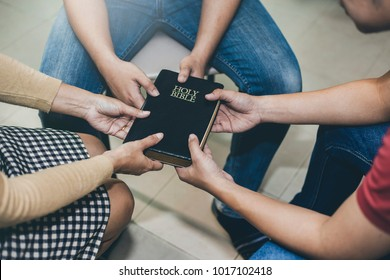 Three people holding bible and pray together, christian group
