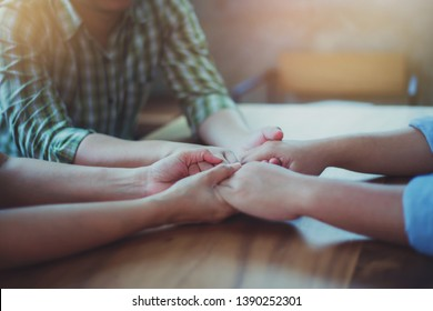 Three people holding hands and prays together on wooden table, Christian pray meeting or team work concept.