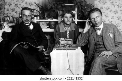 Three people listening to an early radio, c. 1925