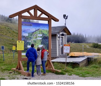 Three people looking at Revelstoke ski information board in the Canadian Rockies, British Columbia Canada. October 2019
