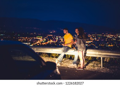 Three people at night are standing and enjoying the city panorama from the road guardrail. Young and careless group in urban environment